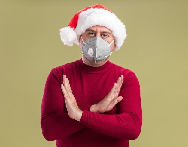 Homem de meia idade com chapéu de papai noel de natal e máscara protetora facial com cara séria fazendo gesto de parada cruzando as mãos em pé sobre a parede verde