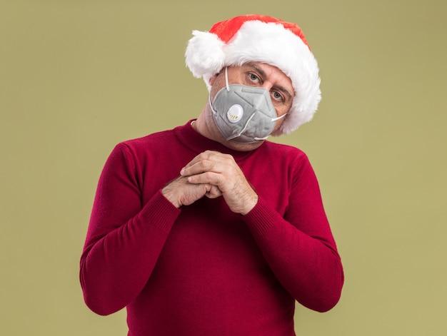 Homem de meia idade com chapéu de papai noel de natal e máscara protetora facial de mãos dadas com rosto sério em pé sobre uma parede verde