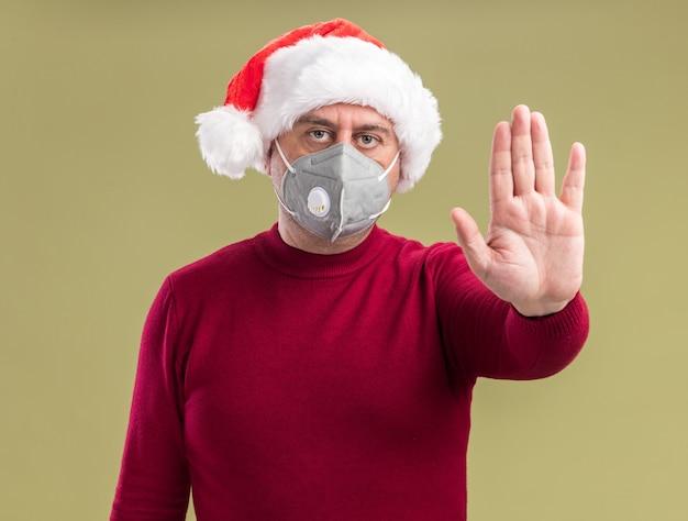 Homem de meia-idade com chapéu de papai noel de natal e máscara protetora facial fazendo gesto de parada com a mão e rosto sério em pé sobre a parede verde