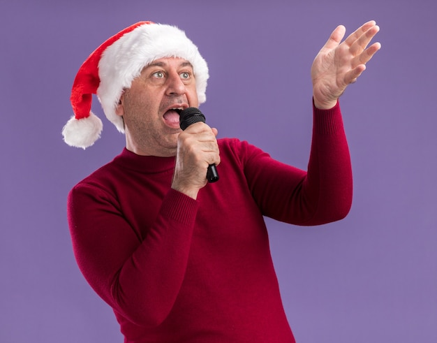 Homem de meia-idade com chapéu de papai noel de natal segurando o microfone cantando feliz e animado em pé sobre um fundo roxo