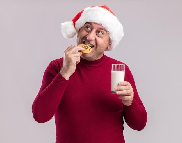 Homem de meia-idade com chapéu de papai noel de natal segurando um copo de leite comendo biscoito e sorrindo feliz e alegre em pé sobre uma parede branca