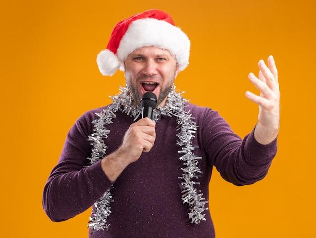 Homem de meia-idade com chapéu de papai noel e guirlanda de ouropel pendurado no pescoço segurando um microfone, olhando para a câmera, mantendo a mão no ar, cantando isolado em um fundo laranja