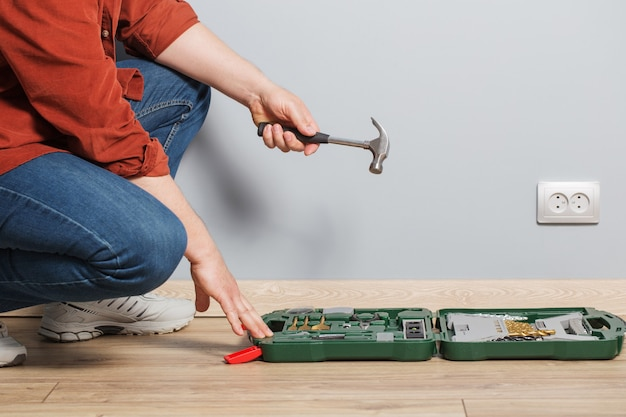 Homem de meia-idade com conjunto de ferramentas de reparo no piso de madeira