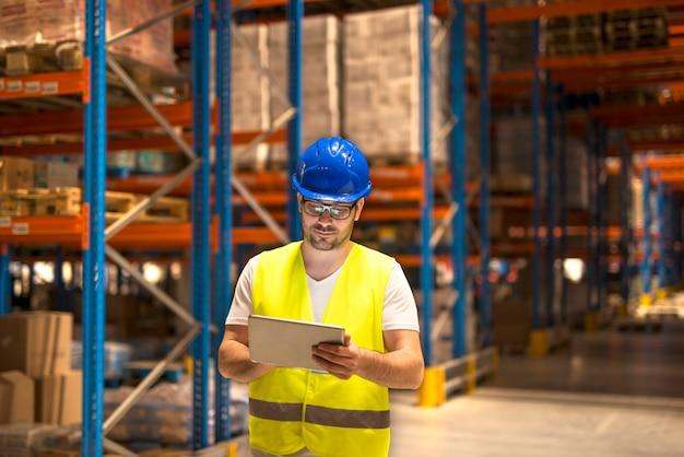 Homem de meia idade com roupa de trabalho de proteção trabalhando em um tablet em um grande armazém de armazenamento