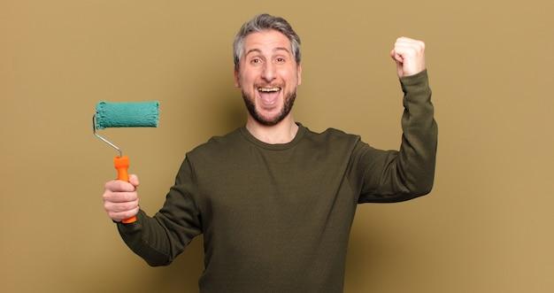 Homem de meia-idade com um conceito de decoração de pintura a rolo