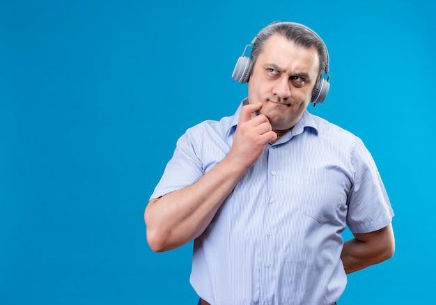 Homem de meia-idade confuso com camisa listrada azul usando fones de ouvido e colocando a mão no queixo tentando resolver o problema em um espaço azul