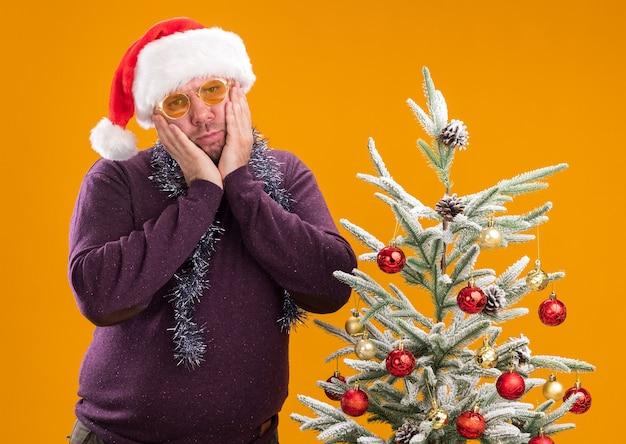 Homem de meia-idade confuso com chapéu de papai noel e guirlanda de ouropel no pescoço, óculos em pé perto da árvore de natal decorada, mantendo as mãos no rosto, olhando para a câmera isolada em fundo laranja