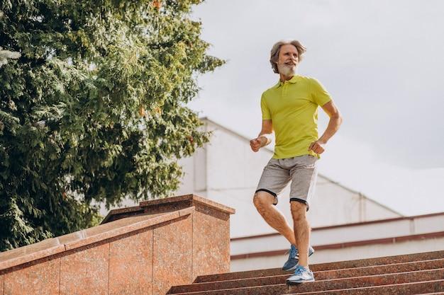 Homem de meia-idade correndo escada abaixo e escada acima
