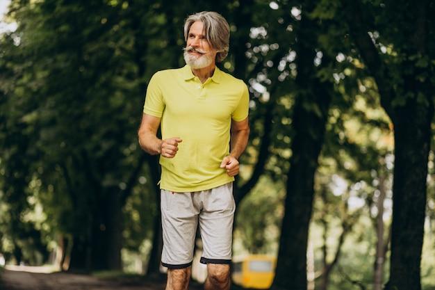 Homem de meia idade correndo na floresta