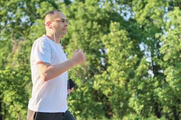 Homem de meia idade correndo no parque, estilo de vida saudável e ativo