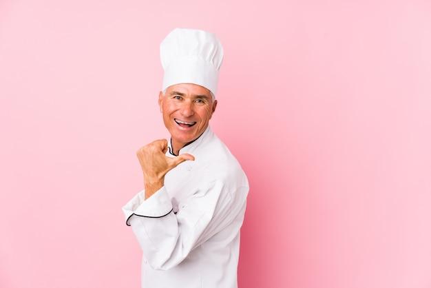 Homem de meia idade cozinheiro aponta com o dedo polegar, rindo e despreocupado.