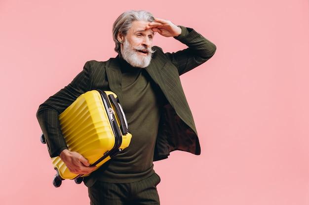 Homem de meia idade de cabelos grisalhos barbudo de terno segurar uma mala amarela na rosa