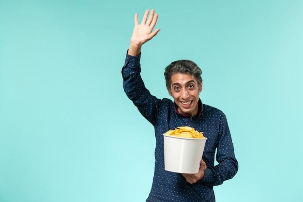 Homem de meia-idade, de frente, segurando batatas cips e acenando em uma superfície azul