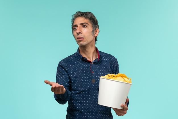 Homem de meia-idade, de frente, segurando uma cesta com batatas cip na superfície azul clara
