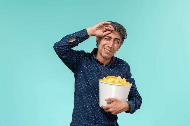 Homem de meia-idade, de frente, segurando uma cesta com cips e assistindo a um filme na superfície azul