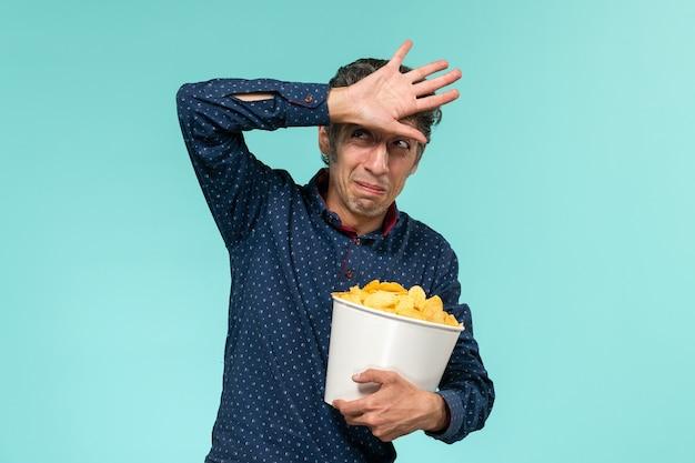 Homem de meia-idade, de frente, segurando uma cesta com cips e assistindo filme na mesa azul