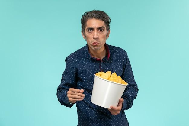 Homem de meia-idade de vista frontal com uma cesta cheia de cips e comendo em uma superfície azul clara