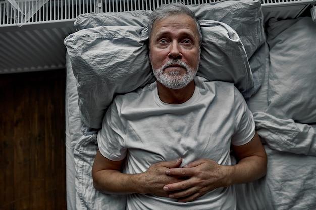 Homem de meia-idade deitado na cama no travesseiro, tendo o distúrbio do sono de insônia. sozinho em casa