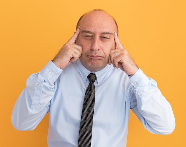 Homem de meia-idade desagradável vestindo camiseta branca com gravata, mostrando gesto de olhos asiáticos isolado em parede laranja