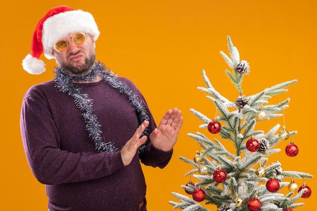 Homem de meia-idade descontente com chapéu de papai noel e guirlanda de ouropel no pescoço, óculos em pé perto da árvore de natal decorada, olhando para a câmera