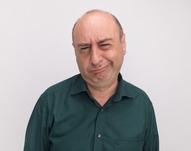 Homem de meia-idade descontente vestindo camiseta verde isolada na parede branca