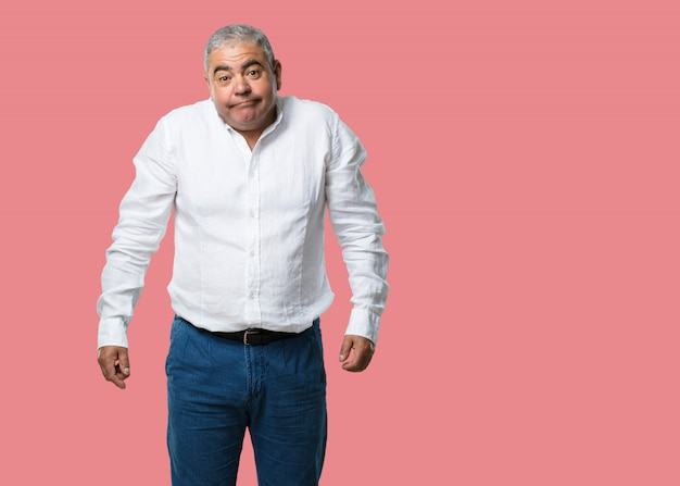 Homem de meia idade duvidando e encolhendo os ombros, conceito de indecisão e insegurança, incerto sobre algo