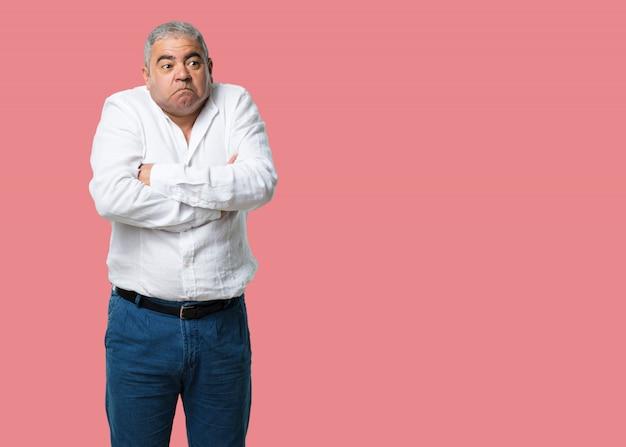Homem de meia idade, duvidando e encolhendo os ombros, conceito de indecisão e insegurança