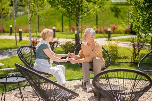 Homem de meia-idade e esposa de mãos dadas