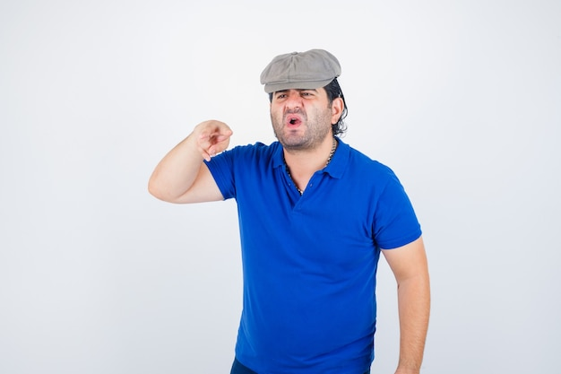 Homem de meia idade em camiseta polo, chapéu de hera mostrando o sinal v e parecendo agressivo, vista frontal.