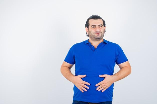Homem de meia idade em camiseta polo, mantendo as mãos na barriga e olhando alegre, vista frontal.