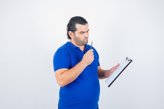 Homem de meia idade em camiseta polo, olhando através da prancheta, segurando o lápis e olhando com foco, vista frontal.