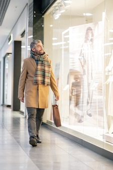 Homem de meia idade em roupas casuais elegantes, olhando para uma das grandes vitrines, enquanto passa com um saco de papel depois de fazer compras