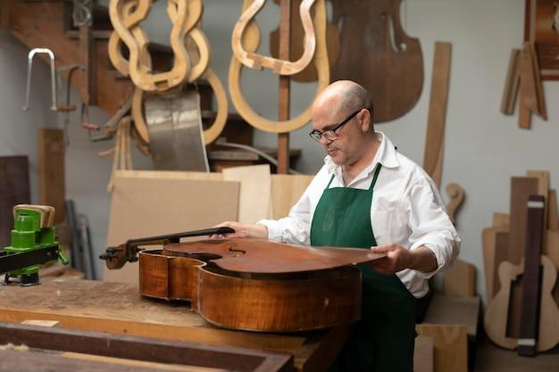 Homem de meia-idade em sua oficina de instrumentos