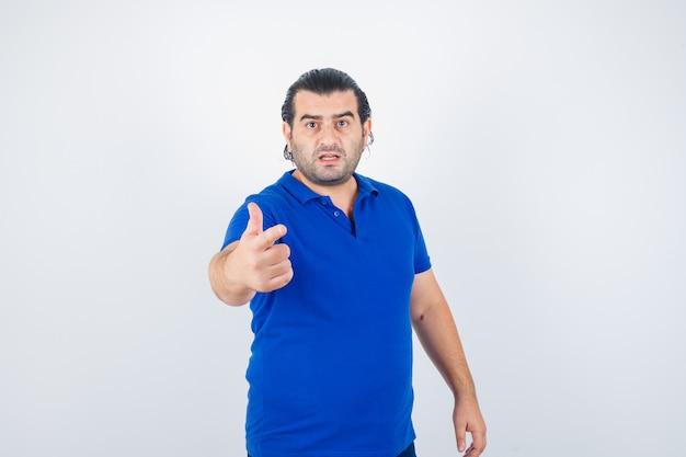 Homem de meia idade em t-shirt azul, apontando para a câmera e olhando perplexo, vista frontal.