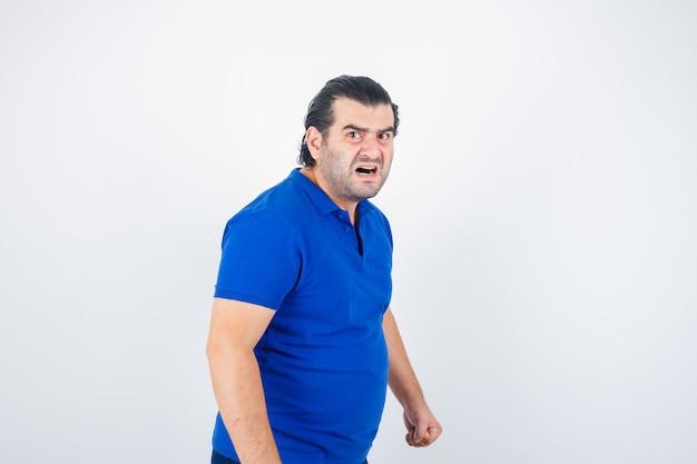 Homem de meia idade em t-shirt polo, olhando para a câmera e olhando furioso, vista frontal.