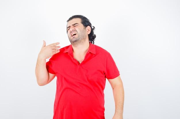 Homem de meia idade em t-shirt vermelha, levantando a mão por cima do ombro e parecendo insatisfeito, vista frontal.
