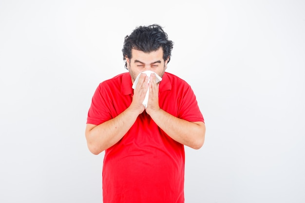 Homem de meia idade em t-shirt vermelha, segurando o lenço, assoando o nariz escorrendo e parecendo insalubre, vista frontal.
