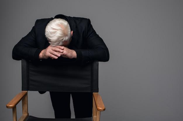Homem de meia idade emocional em um terno preto está chateado.