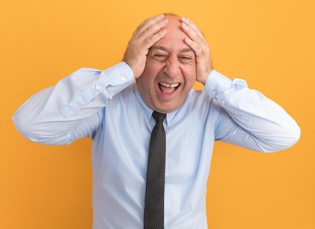 Homem de meia-idade empolgado vestindo camiseta branca com gravata agarrada na cabeça isolada na parede laranja