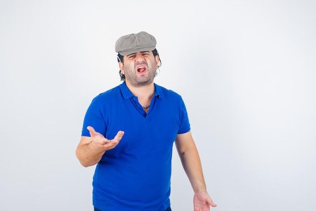 Homem de meia-idade esticando a mão de maneira questionadora com camiseta pólo e chapéu de hera, parecendo zangado