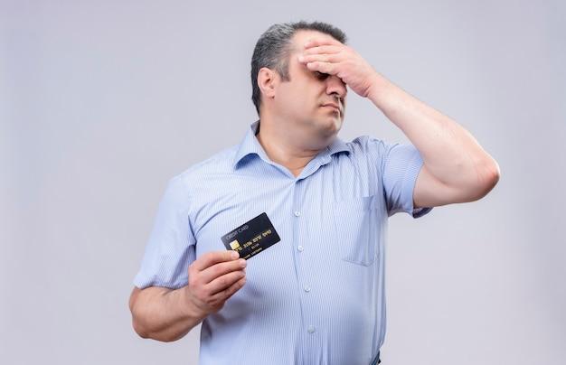 Homem de meia-idade estressado, vestindo uma camisa listrada azul com a mão na cabeça, mostrando o cartão de crédito em pé sobre um fundo branco