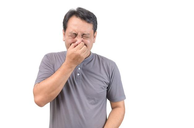 Homem de meia idade fazendo gestos cheira mal isolado no fundo branco. expressão facial. homem cobre o nariz com a mão, cheira algo horrível