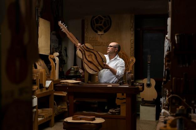 Homem de meia-idade fazendo instrumentos em sua oficina sozinho