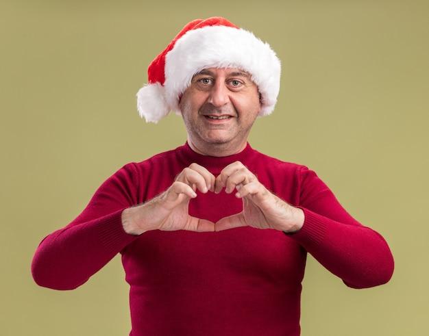 Homem de meia idade feliz com chapéu de papai noel de natal fazendo gesto de coração e sorrindo alegremente em pé sobre um fundo verde