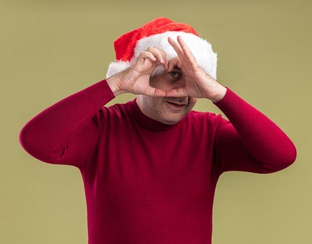 Homem de meia-idade feliz com chapéu de papai noel fazendo gesto de coração e sorrindo alegremente em pé sobre a parede verde