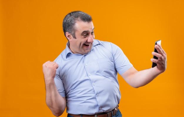 Homem de meia-idade feliz e animado, vestindo uma camisa azul listrada com listras verticais, olhando para o celular e levantando a mão em um gesto de punho cerrado enquanto está de pé sobre uma parte traseira laranja