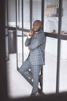 Homem de meia-idade feliz e pensativo em um terno sorri o cara afro-americano ficou pensativo