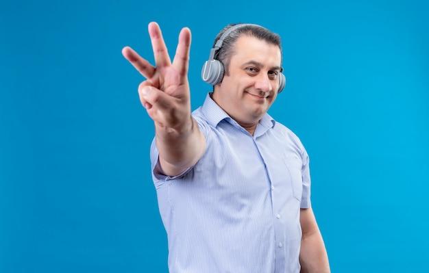 Homem de meia-idade feliz e positivo em uma camisa listrada azul em fones de ouvido, mostrando com os dedos número seis em um espaço azul