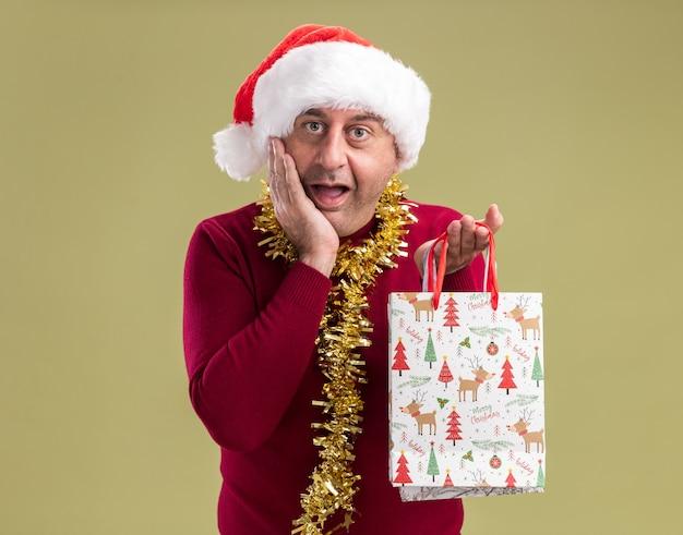 Homem de meia-idade feliz usando chapéu de papai noel com enfeites de natal ao redor do pescoço e segurando sacolas de papel com presentes de natal sorrindo alegremente em pé sobre a parede verde