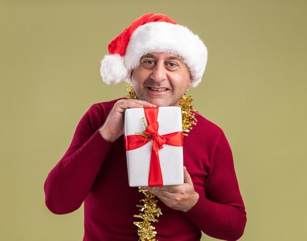 Homem de meia-idade feliz usando chapéu de papai noel com enfeites de natal no pescoço e segurando um presente de natal com um sorriso no rosto em pé sobre a parede verde